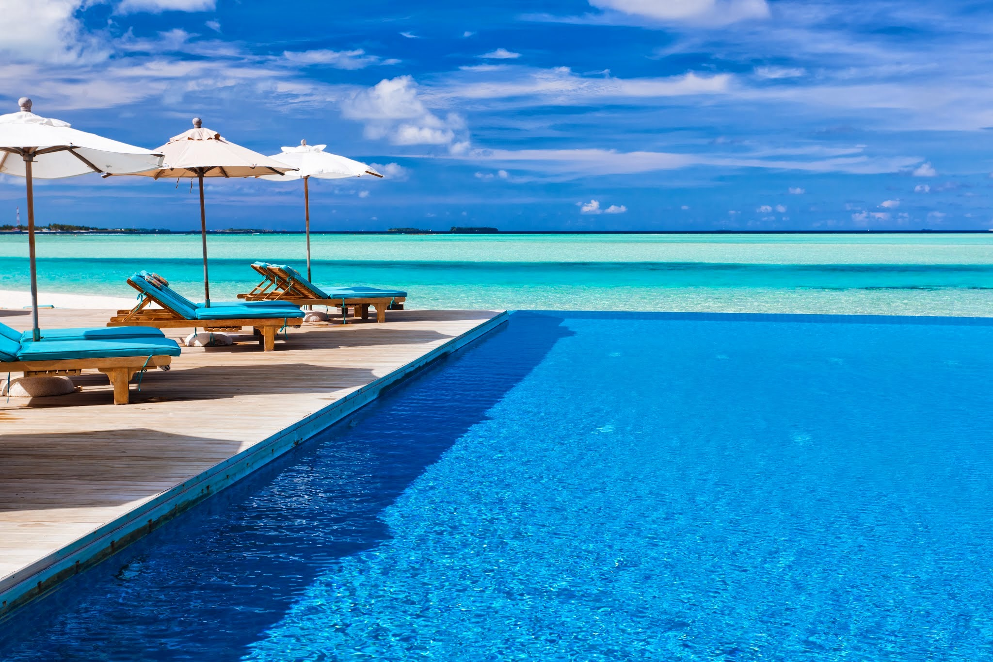 Deck chairs and infinity pool over amazing tropical lagoon